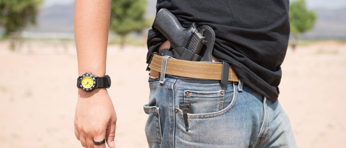 Man with holster pistol in jeans [Shutterstock/Ambrosia Studios]