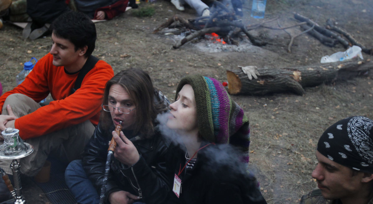 "People smoke a hookah as they sit by a fire during the ""Pustiye Holmi"" (Empty Hills) autumnal open-air hippie-style music festival outside the village of Koltsovo, some 210 km (129 miles) southwest of Moscow, October 2, 2010. Several thousands of people spent two nights in the open air to enjoy alternative arts and music. Picture taken October 2, 2010. REUTERS/Denis Sinyakov"