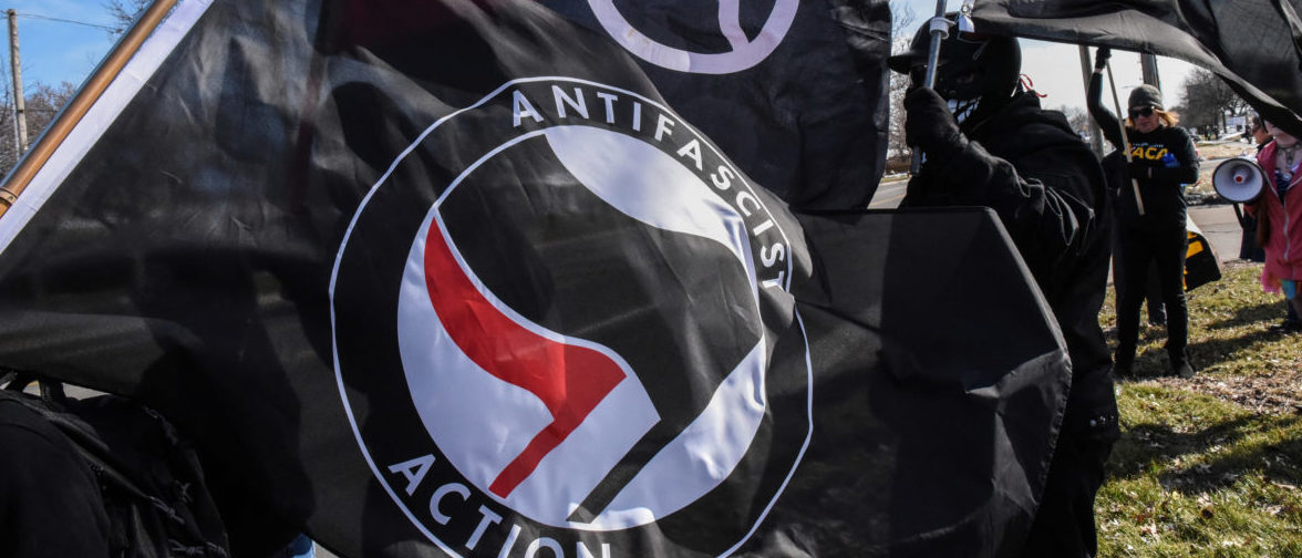 Members of the Great Lakes anti-fascist organization (Antifa) fly flags during a protest against the Alt-right outside a hotel in Warren, Michigan, U.S., March 4, 2018. REUTERS/Stephanie Keith - RC1B5E31E310