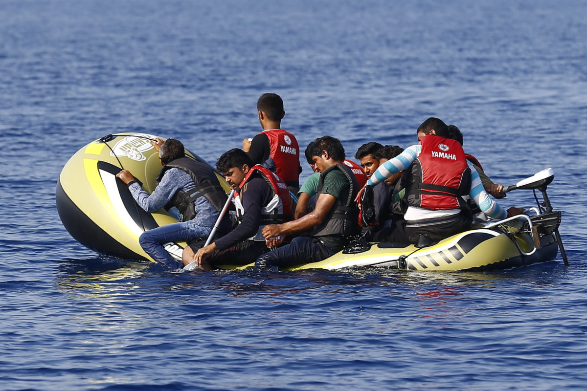 Migrants in a dinghy with a small motor paddle their craft after leaving Bodrum, Turkey, in the hopes of crossing the Mediterranean Sea to reach the Greek Island of Kos, September 19, 2015. Of the record total of 432,761 refugees and migrants making the perilous journey across the Mediterranean to Europe so far this year, an estimated 309,000 people had arrived by sea in Greece, the International Organization for Migration (IMO) said. About half of those crossing the Mediterranean are Syrians fleeing civil war, according to the United Nations refugee agency. REUTERS/Umit Bektas