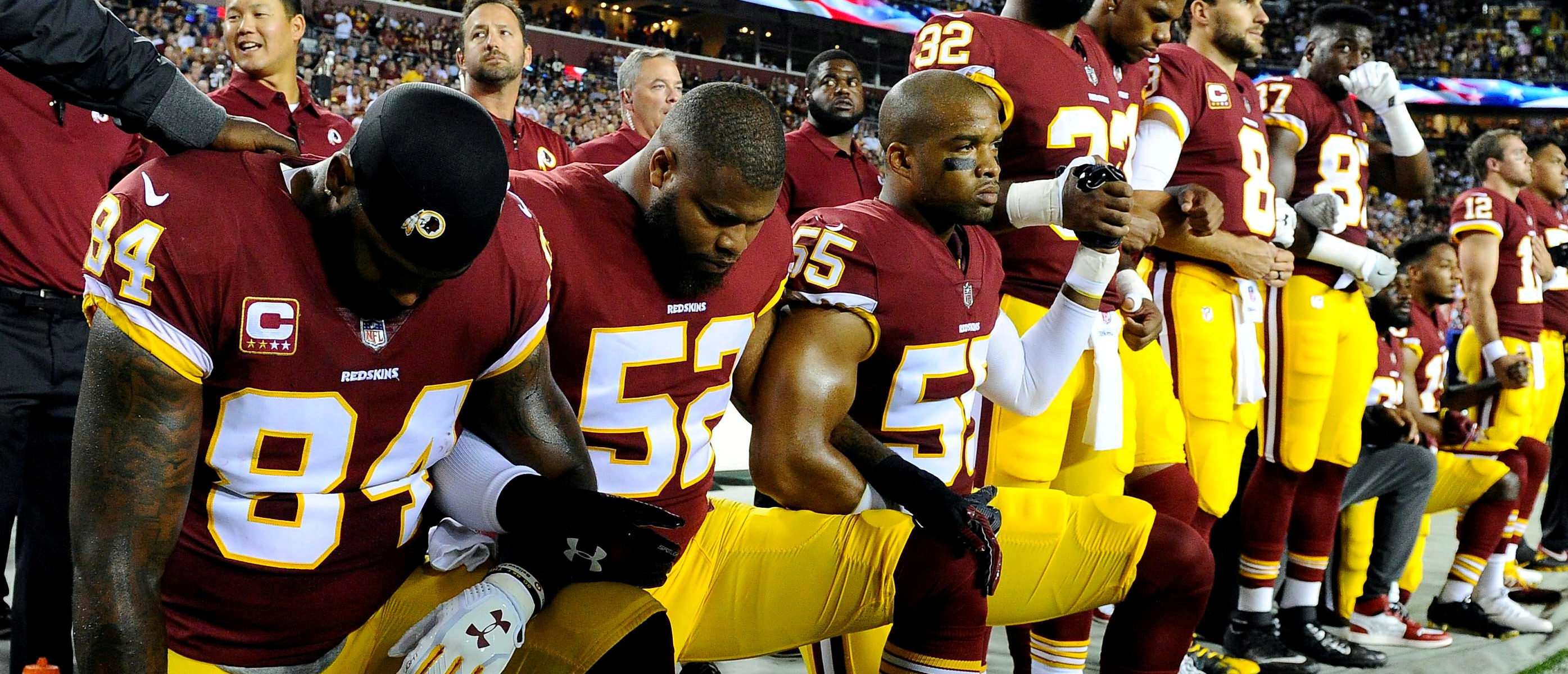FILE PHOTO: Washington Redskins tight end Niles Paul (84) and linebacker Ryan Anderson (52) and Washington Redskins linebacker Chris Carter (55) kneel with teammates during the playing of the national anthem before the game between the Washington Redskins and the Oakland Raiders at FedEx Field in Landover, MD, U.S., September 24, 2017. Mandatory Credit: Brad Mills-USA TODAY Sports/File Photo - RC138C51C170