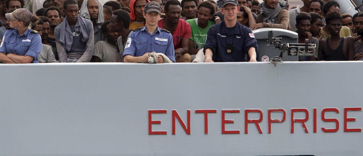Migrants arrive on the British vessel HMS Enterprise before disembarking in the Sicilian harbour of Catania, Italy, October 6, 2015. REUTERS/Antonio Parrinello