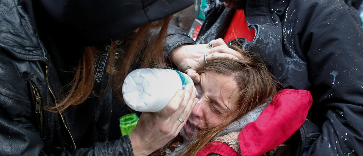 An activist demonstrating against U.S. President Donald Trump is helped after being hit by pepper spray on the sidelines of the inauguration in Washington, D.C. January 20, 2017. REUTERS/Adrees Latif