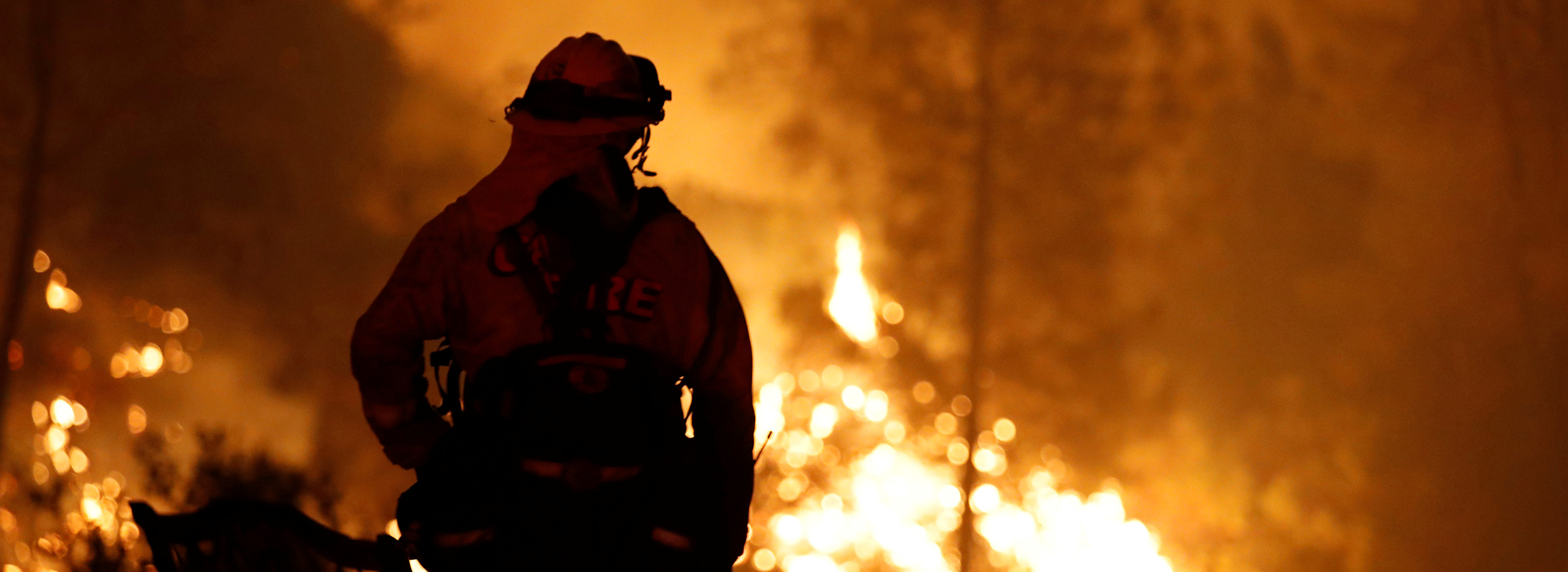 A firefighter watches flames advance up a hill towards homes as crews battle the Carr Fire, west of Redding, California, U.S. July 27, 2018. REUTERS/Fred Greaves - RC154E260610