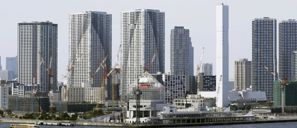 Photo taken June 28, 2018, shows high-rise condominiums behind the athletes' village for the 2020 Tokyo Olympics and Paralympics, under construction, in Tokyo's Harumi and Kachidoki waterfront areas. (Photo by Kyodo News via Getty Images)