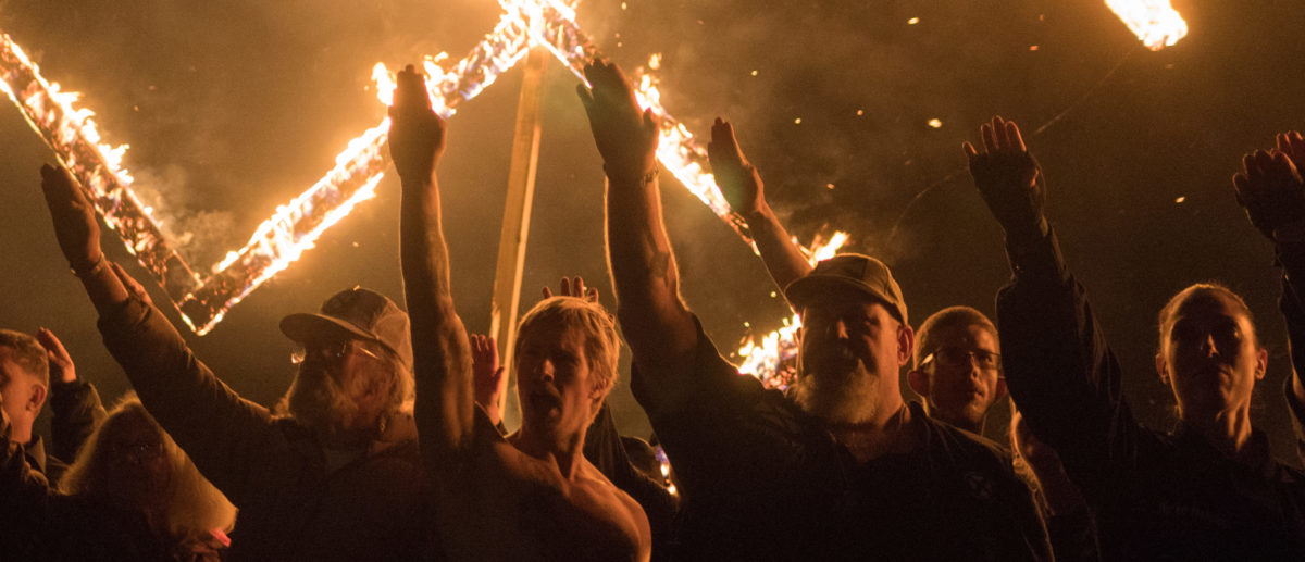 Supporters of the National Socialist Movement, a white nationalist political group, give Nazi salutes while taking part in a swastika burning at an undisclosed location in Georgia, U.S. on April 21, 2018. Picture taken on April 21, 2018. REUTERS/Go Nakamura