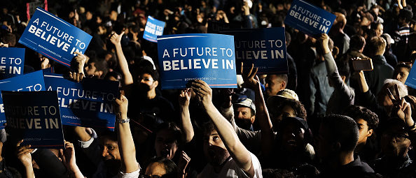 NEW YORK, NY - APRIL 18: People cheer as Democratic Presidential candidate Bernie Sanders walks on stage at a campaign rally on the eve of the New York primary, April 18, 2016 in the Queens borough of New York City. While Sanders is still behind in the delegate count with Hillary Clinton, he has energized many young and liberal voters around the country. New York holds its primary this Tuesday. (Photo by Spencer Platt/Getty Images)