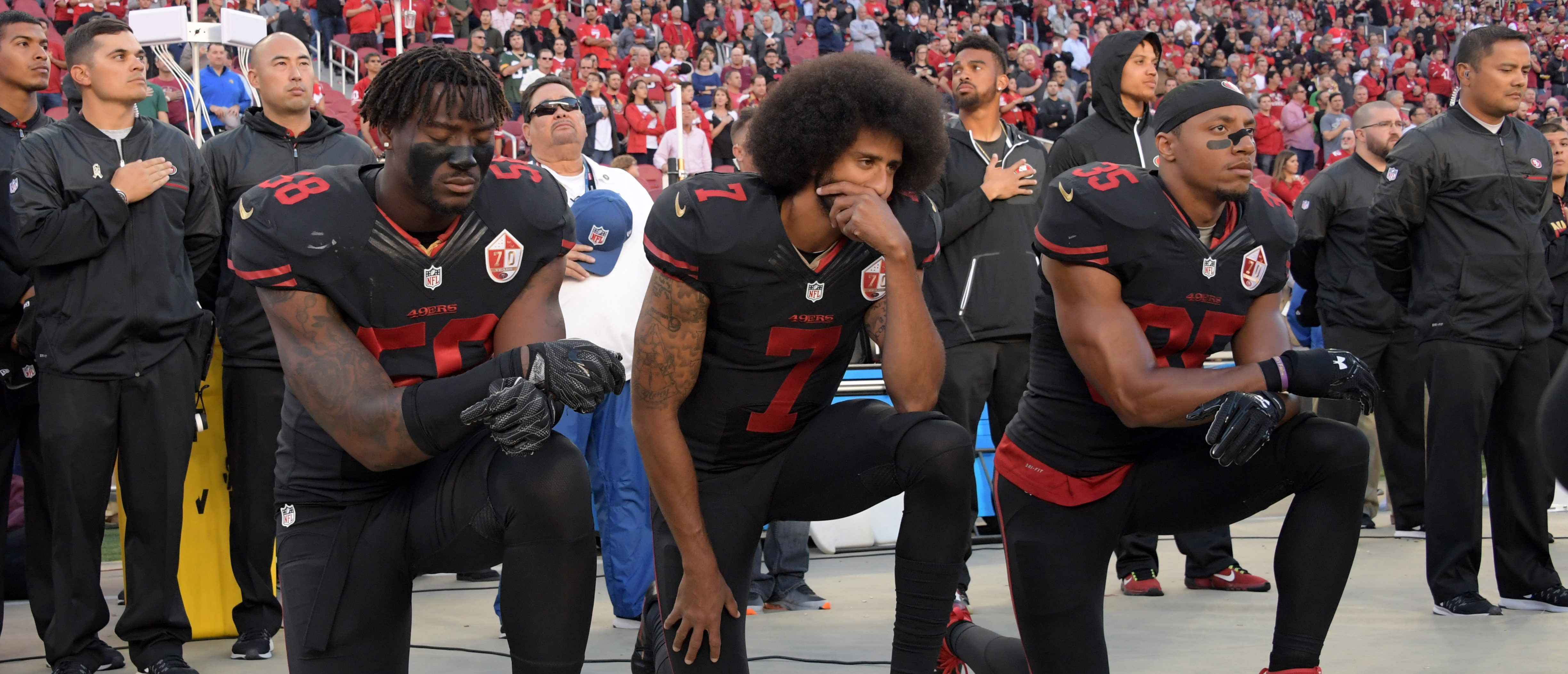 Oct 6, 2016; Santa Clara, CA, USA; San Francisco 49ers outside linebacker Eli Harold (58), quarterback Colin Kaepernick (7) and free safety Eric Reid (35) kneel in protest during the playing of the national anthem before a NFL game against the Arizona Cardinals at Levi's Stadium. Mandatory Credit: Kirby Lee-USA TODAY Sports