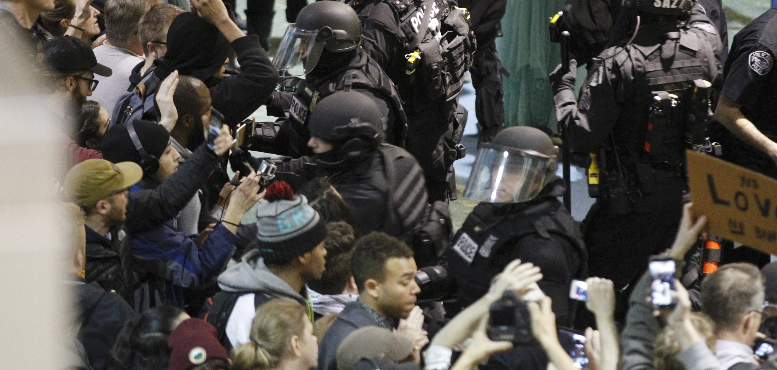 Riot police push activists gathered at Portland International Airport to protest against President Donald Trump's executive action travel ban in Portland, Oregon, U.S. January 29, 2017. REUTERS/Steve Dipaola