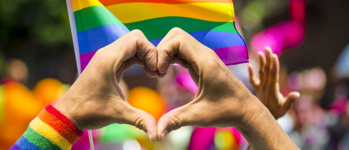 Supporting hands make heart sign and wave in front of a rainbow flag flying on the sidelines of a summer gay pride parade (SHUTTERSTOCK: By lazyllama)