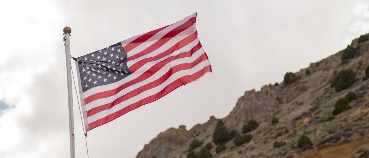 An American flag is waving in the wind around the American landscape. SHUTTERSTOCK/ Robert Guio