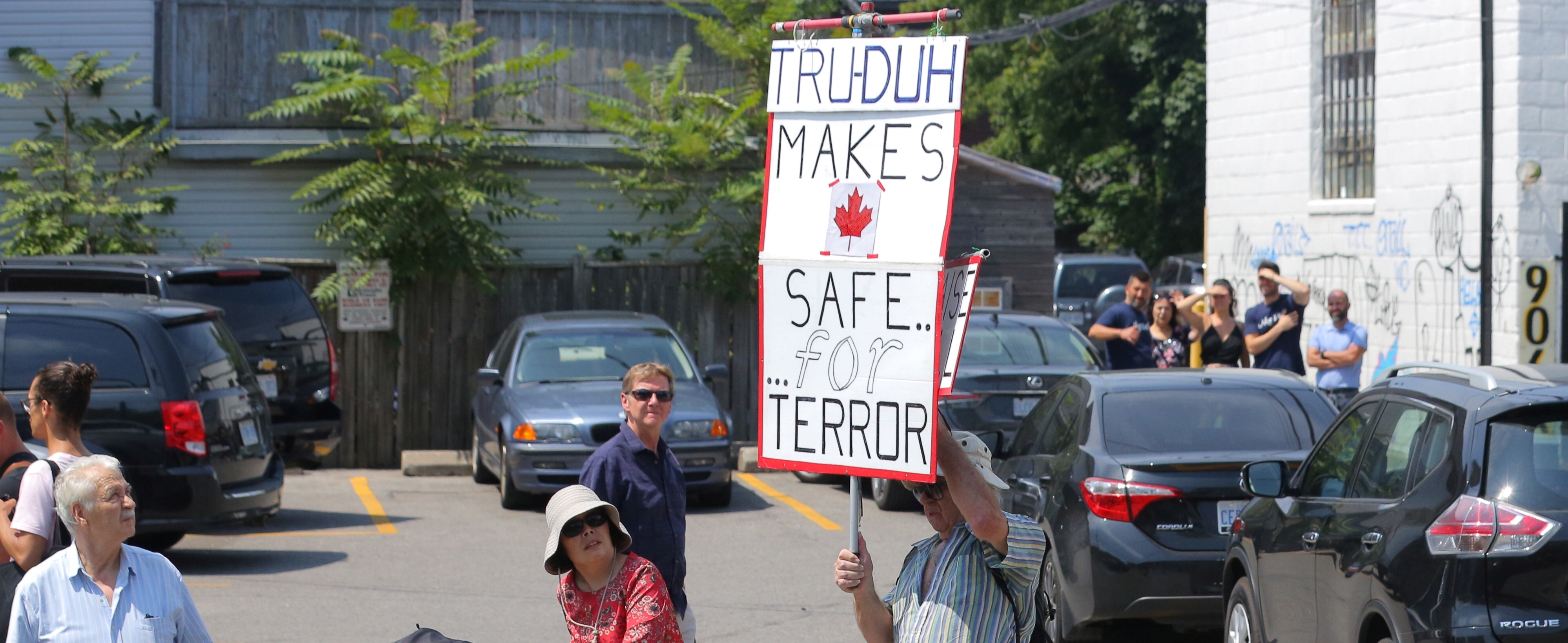 A protester holds a sign during Canada's Prime Minister Justin Trudeau's visit to the site of the mass shooting at Alexander the Great Parkette on Danforth Avenue in Toronto, Ontario, Canada, July 30, 2018. REUTERS/Chris Helgren - RC1756EE9FB0
