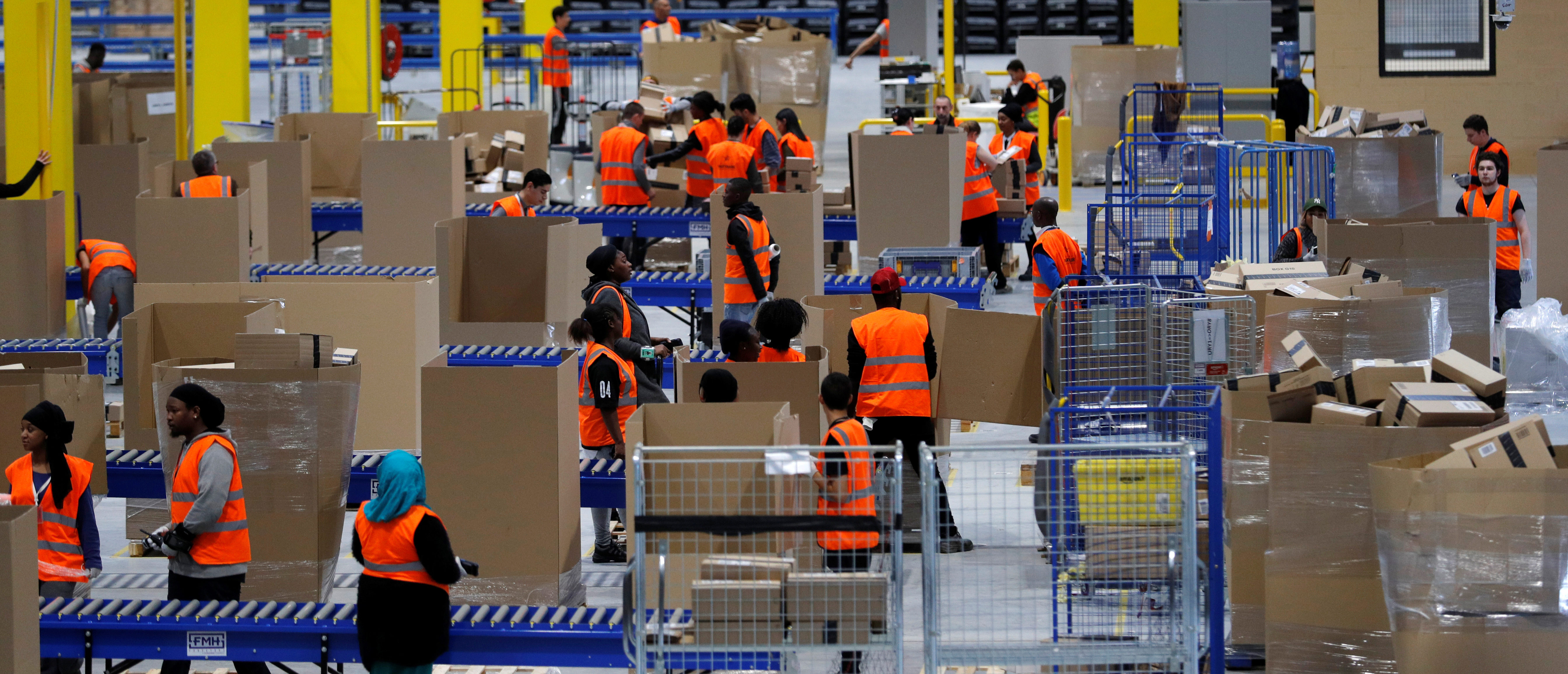 Employees work at the Amazon distribution center warehouse in Saran, near Orleans, France, November 22, 2016. REUTERS/Philippe Wojazer
