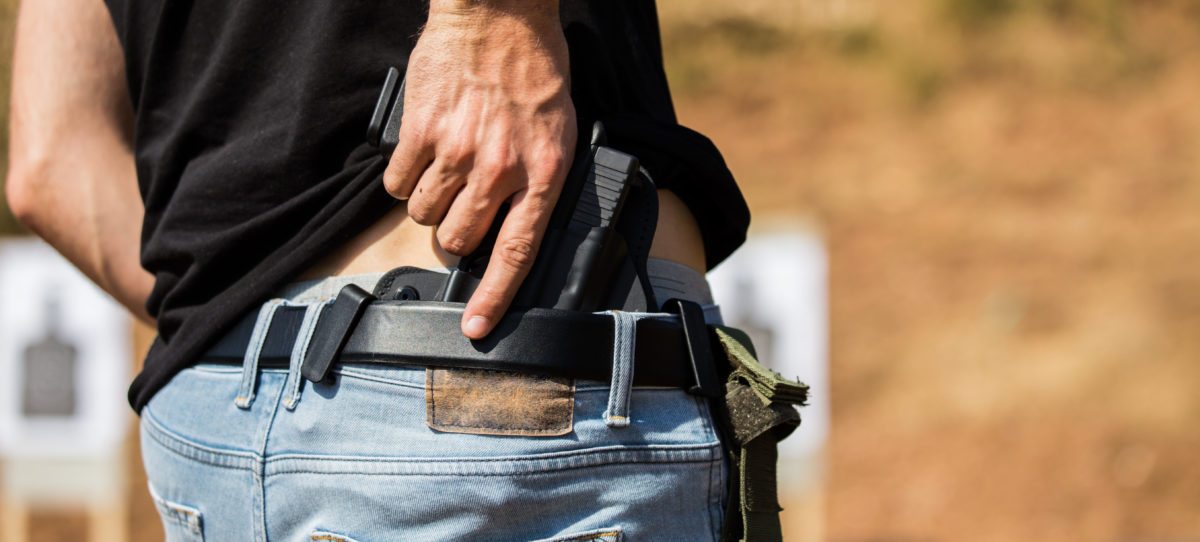The man hid the gun behind his back. [Shutterstock/Hajrudin Hodzic]