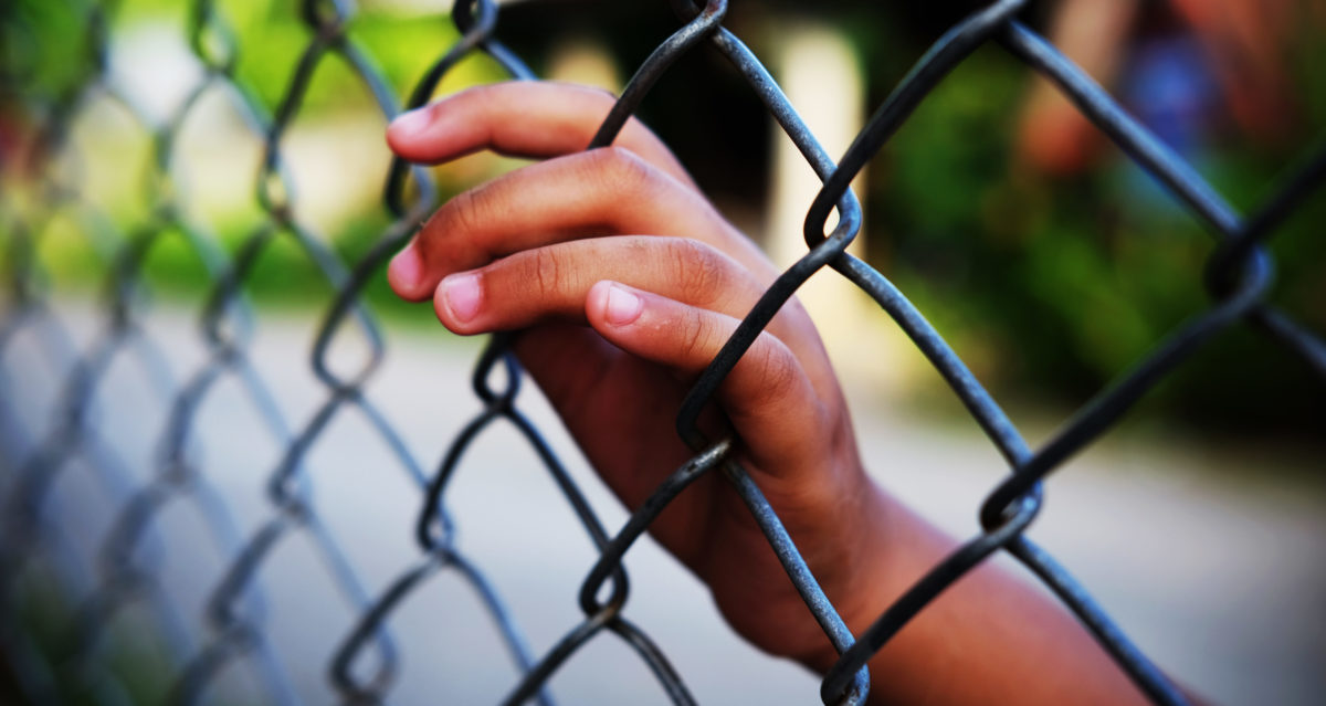 Hand in house of detention concept, vignette effect and selective focus [Shutterstock/chatiyanon]