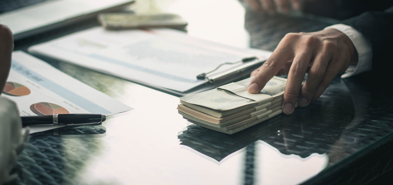 Donor Offering Money (Shutterstock/bluedog studio)