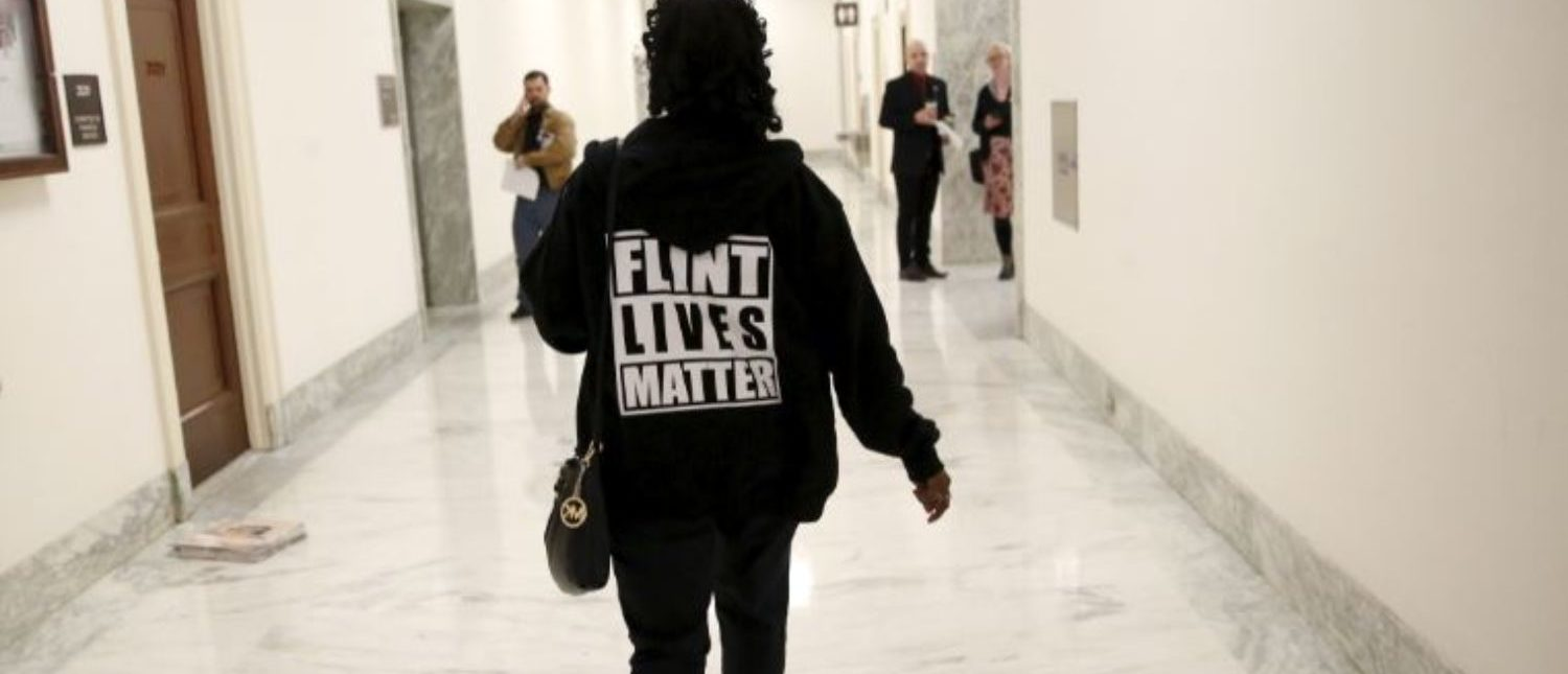 """A woman with a """"Flint Lives Matter"""" shirt walks toward a hearing room where Michigan Governor Rick Snyder and EPA Administrator Gina McCarthy will testify before a House Oversight and government Reform hearing on """"Examining Federal Administration of the Safe Drinking Water Act in Flint, Michigan, Part III"""" on Capitol Hill in Washington, DC, U.S. on March 17, 2016. REUTERS/Kevin Lamarque/File Photo"""