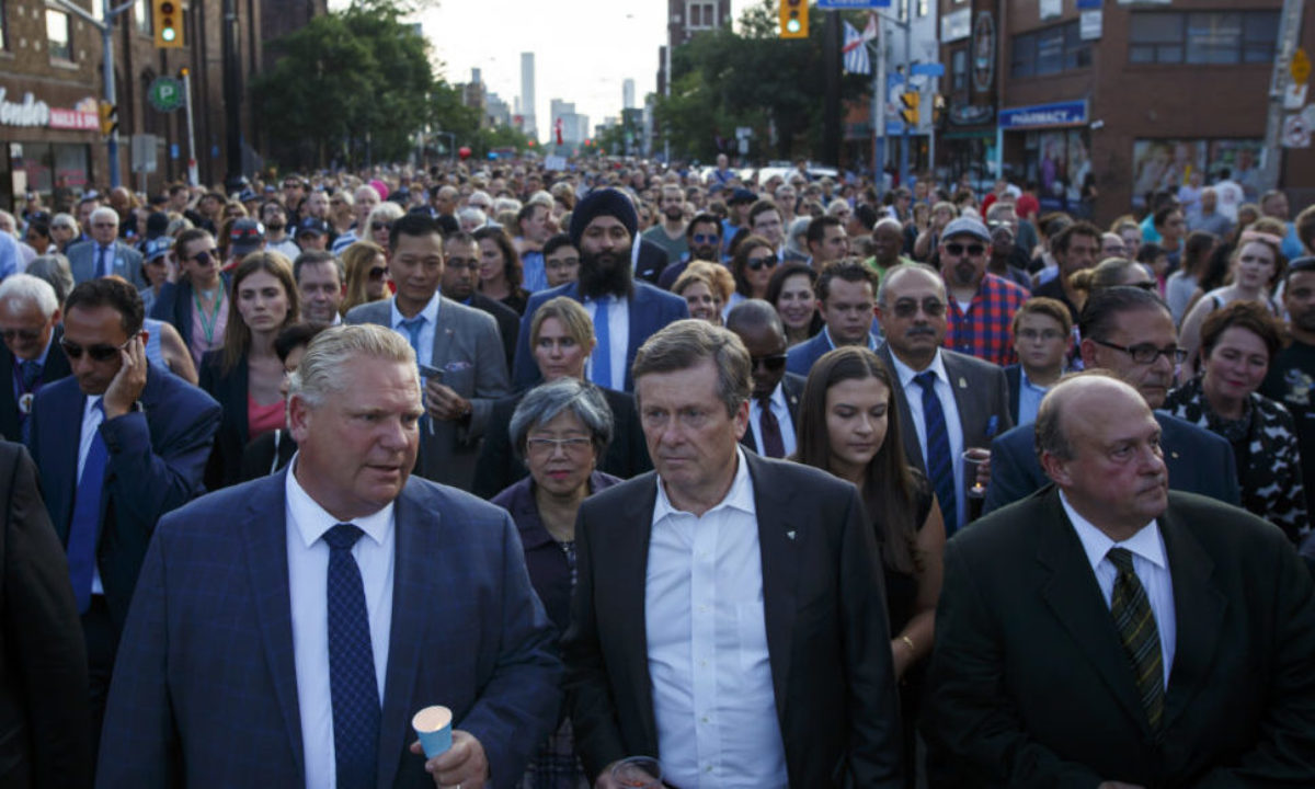 TORONTO, ON - JULY 25: Ontario Premier Doug Ford, left, and Toronto Mayor John Tory march along Danforth Ave. during a vigil for victims of Sunday night's mass shooting on Danforth Ave. on July 25, 2018 in Toronto, Canada. (Photo by Cole Burston/Getty Images)