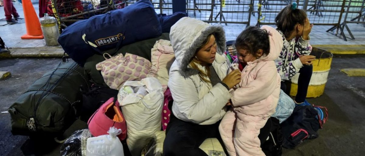 """A Venezuelan migrant woman waits with her daughter outside the Ecuadoran Migration offices, at the Rumichaca International Bridge in Tulcan, Ecuador, on August 19, 2018, for an authorization that allows them to enter Ecuador. - Bogota said on August 17 it was """"worried"""" that tightened Ecuadorean entry requirements for Venezuelans fleeing the economic and political crisis would leave thousands stranded in Colombia. Ecuador announced on Thursday that Venezuelans entering the country would need to show passports from Saturday onwards, a document many are not carrying. And Peru followed suit on Friday, announcing an identical measure due to begin a week later. (Photo by Luis ROBAYO / AFP) (Photo credit should read LUIS ROBAYO/AFP/Getty Images)"""