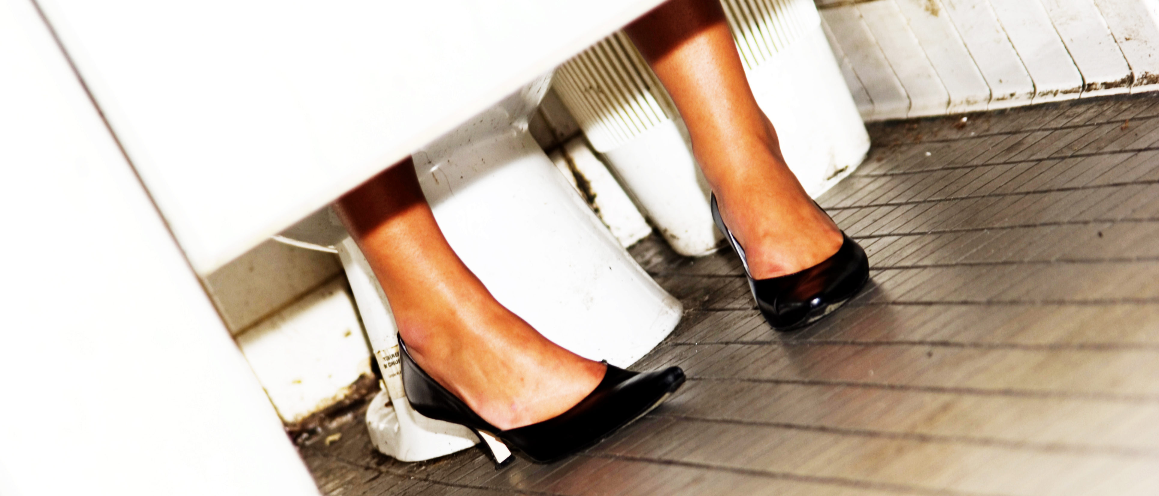 Girls's feet peeping out of bathroom stall (Shutterstock/GWImages)