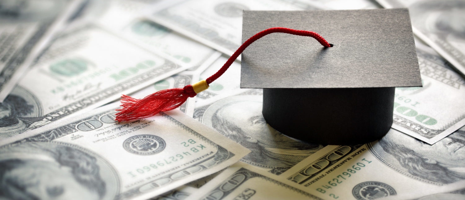 Graduation mortar board cap on one hundred dollar bills concept for the cost of a college and university education. Source: Brian A Jackson/Shutterstock