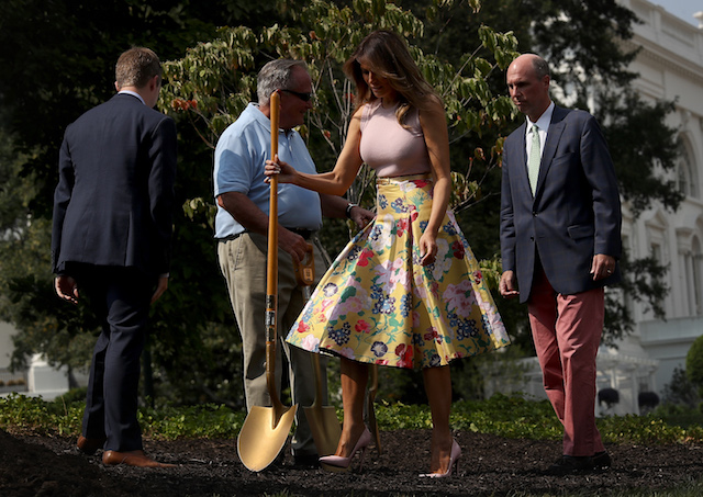 U.S. first lady Melania Trump (2nd R) and Richard Gatchell Jr. (R), fifth generation grandson of President James Monroe, participate in a tree planting ceremony on the south grounds of the White House August 27, 2018 in Washington, DC. The tree comes from the original Eisenhower Oak located near the Kennedy Garden that was excavated from the grounds earlier this year. (Photo by Win McNamee/Getty Images)