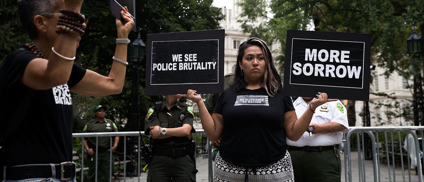 Lorena Ambrosio, from Brooklyn, New York, holds up signs during a protest against police brutality at City Hall Park, August 1, 2016 in New York City. The protest was organized by Millions March NYC, who are calling on Mayor Bill de Blasio to fire NYPD Commissioner Bill Bratton and end 'broken windows policing. The group is claiming they will stay in City Hall Park until their demands are met. (Photo by Drew Angerer/Getty Images)