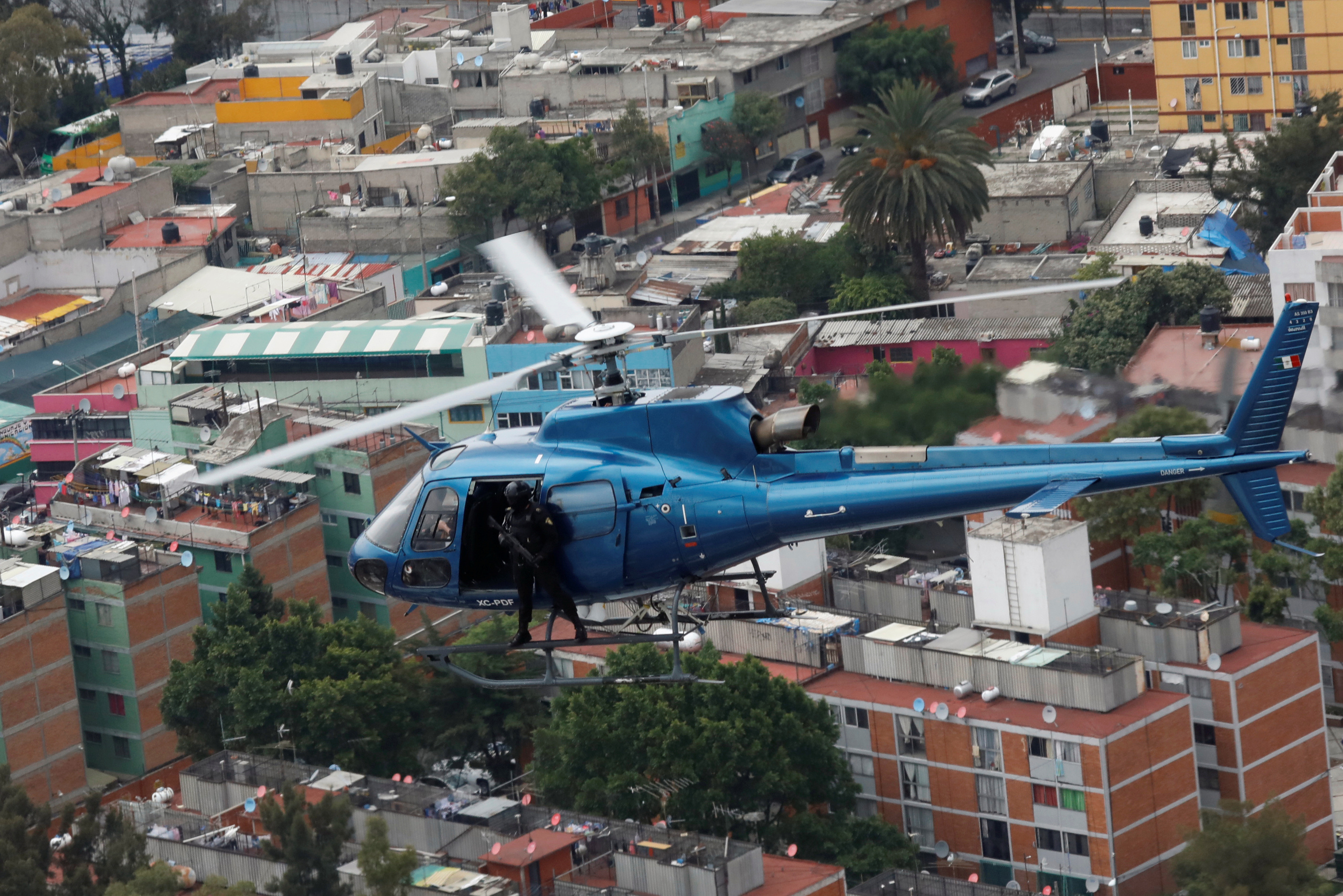 """Police officers, members of a team known as """"Condores"""", stand by the door of the helicopter during a patrol of the city, part of a new strategy to combat the crime in Mexico City, Mexico August 3, 2018. Picture taken August 3, 2018. REUTERS/Carlos Jasso - RC1ADE095290"""