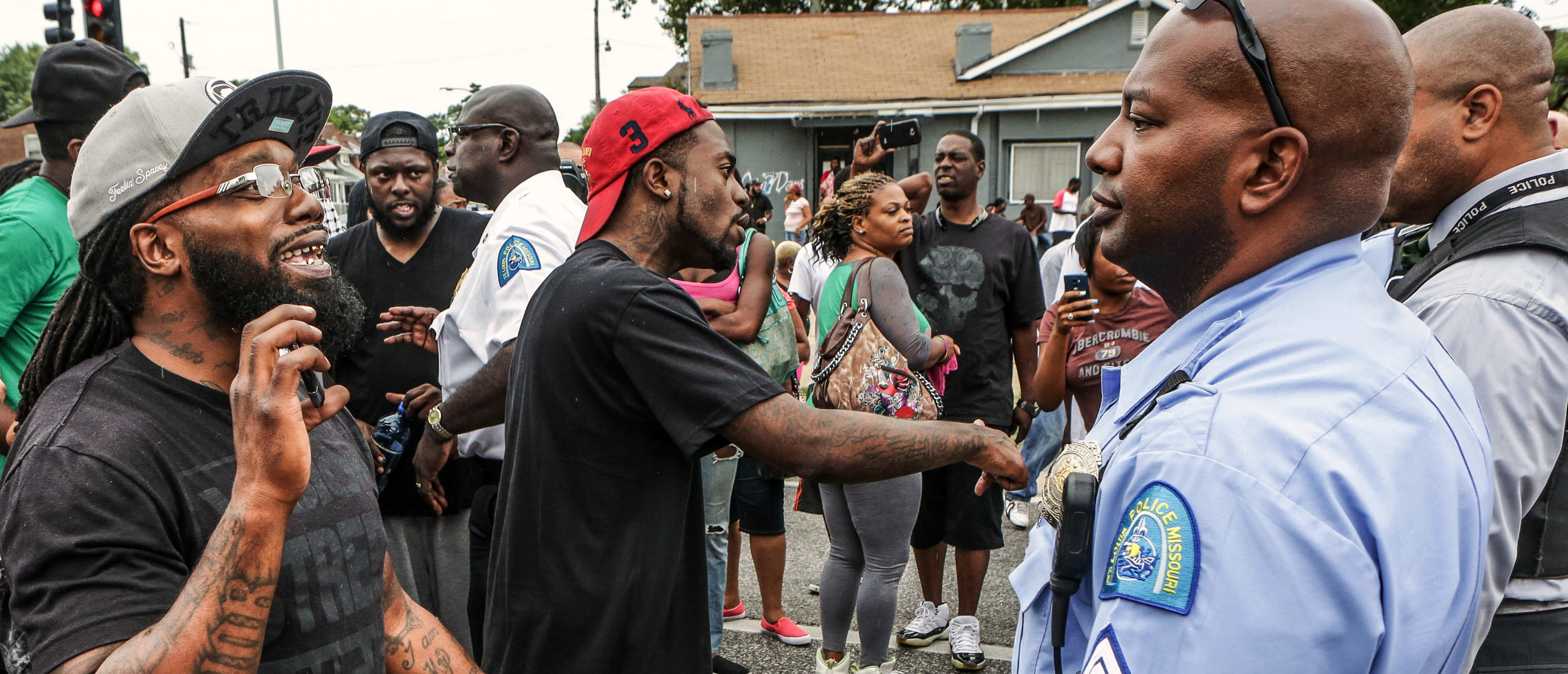 Area residents talk to police after a shooting incident in St. Louis, Missouri August 19, 2015. Police fatally shot a black man they say pointed a gun at them, drawing angry crowds and recalling the racial tensions sparked by the killing of an unarmed African-American teen in nearby Ferguson, Missouri, just over a year ago. REUTERS/Lawrence Bryant