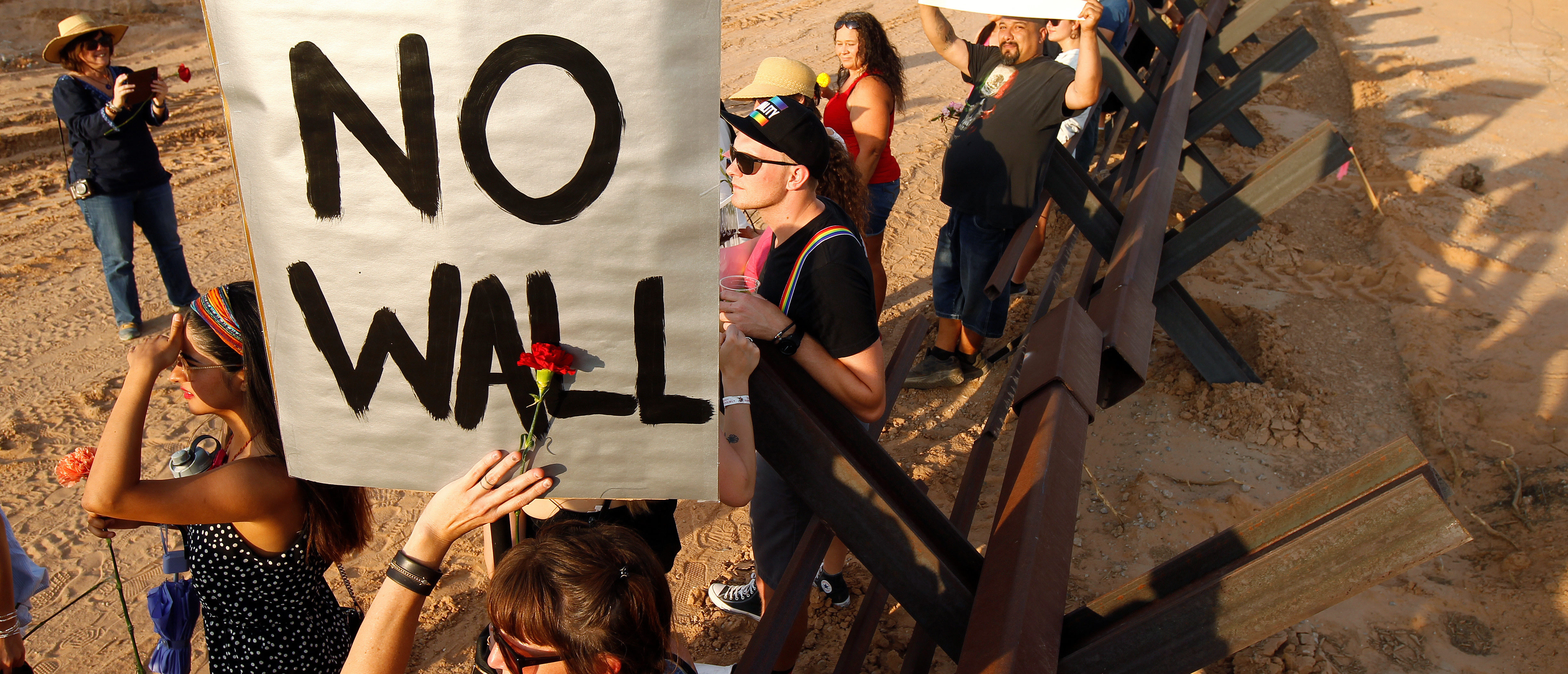 Demonstrators hold up placards during a protest against the border wall and the militarization of the border at a new section of the bollard wall in Santa Teresa, New Mexico, as seen from the Mexican side of the border in San Jeronimo, on the outskirts of Ciudad Juarez, Mexico June 2, 2018. REUTERS/Jose Luis Gonzalez - RC1573585AF0