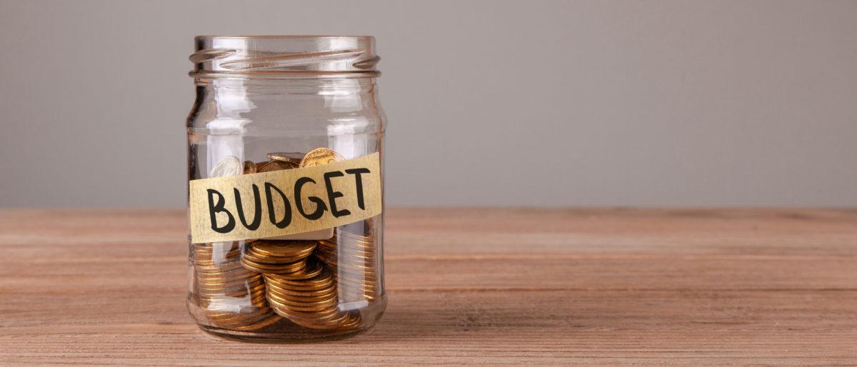 Someone saves money in a jar. Shutterstock image via user ADragan