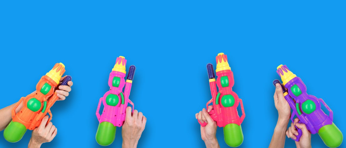 Hands holding gun water toy on blue background. Shutterstock/ Trum Ronnarong