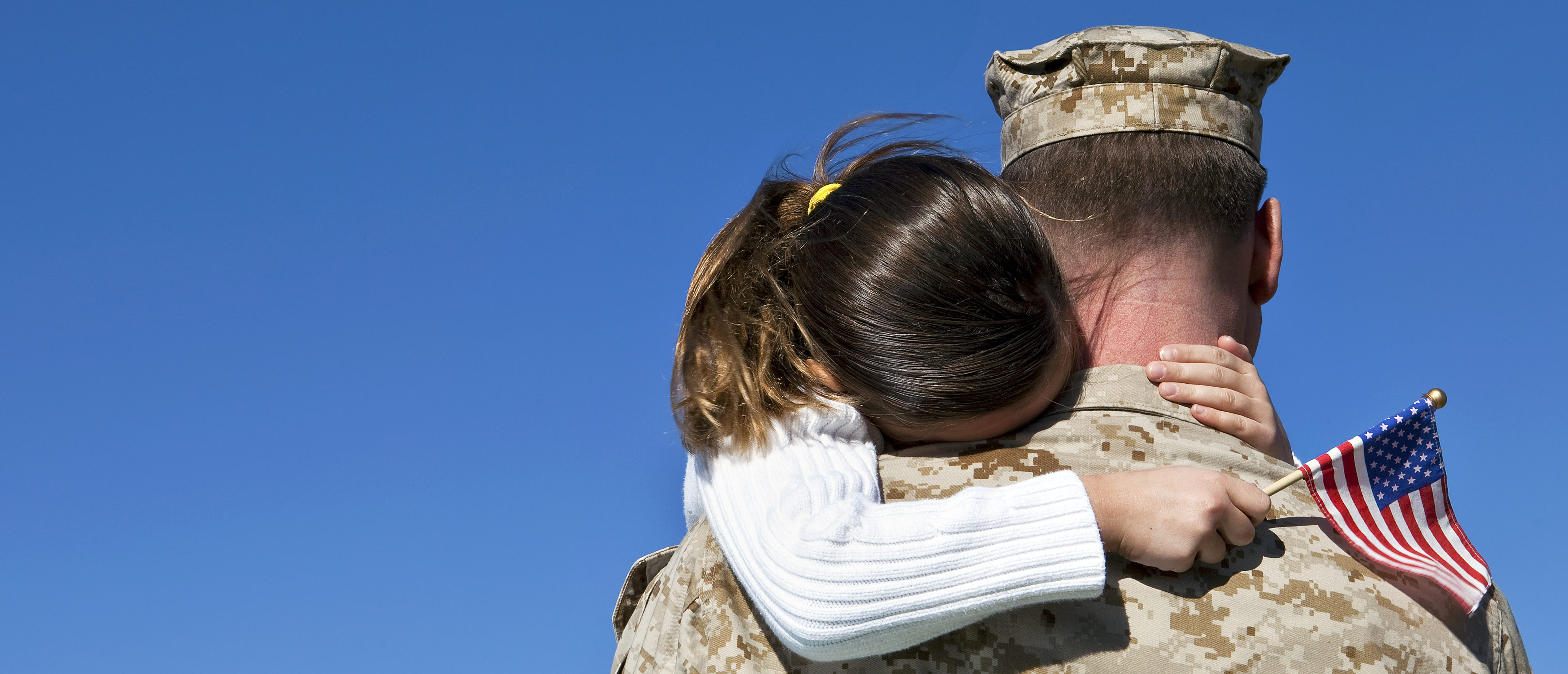 Military man hugs daughter, Shutterstock/ By Straight 8 Photography