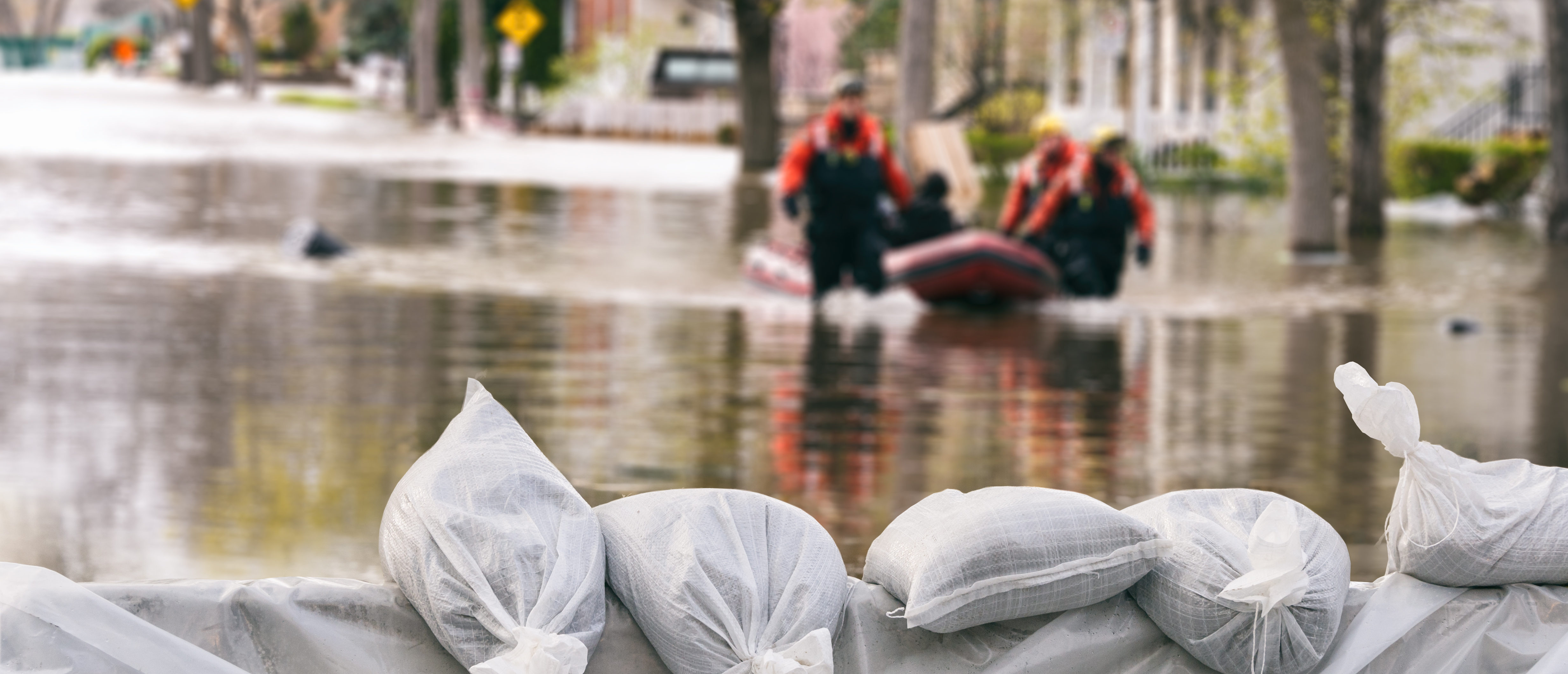 Flood Protection Sandbags with flooded homes in the background (Montage). (Marc Bruxelle/Shutterstock)