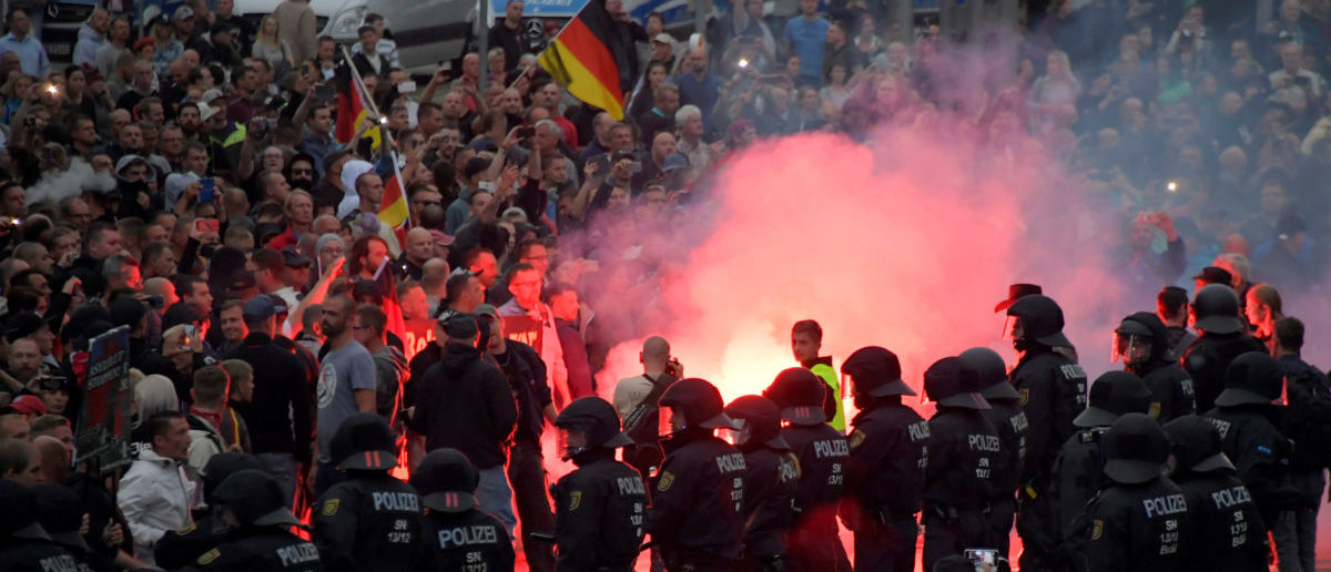Riot policemen stand guard as the right-wing supporters protest after a German man was stabbed last weekend in Chemnitz, Germany, August 27, 2018. REUTERS/Matthias Rietschel