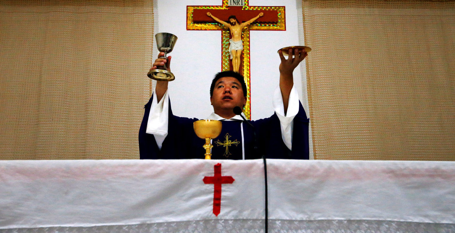 FILE PHOTO: Catholic priest Liu Yong Wang performs holy communion in a make-shift chapel in the village of Bai Gu Tun, located on the outskirts of the city of Tianjin, around 70 km (43 miles) south-east of Beijing July 17, 2012.Reuters/File Photo