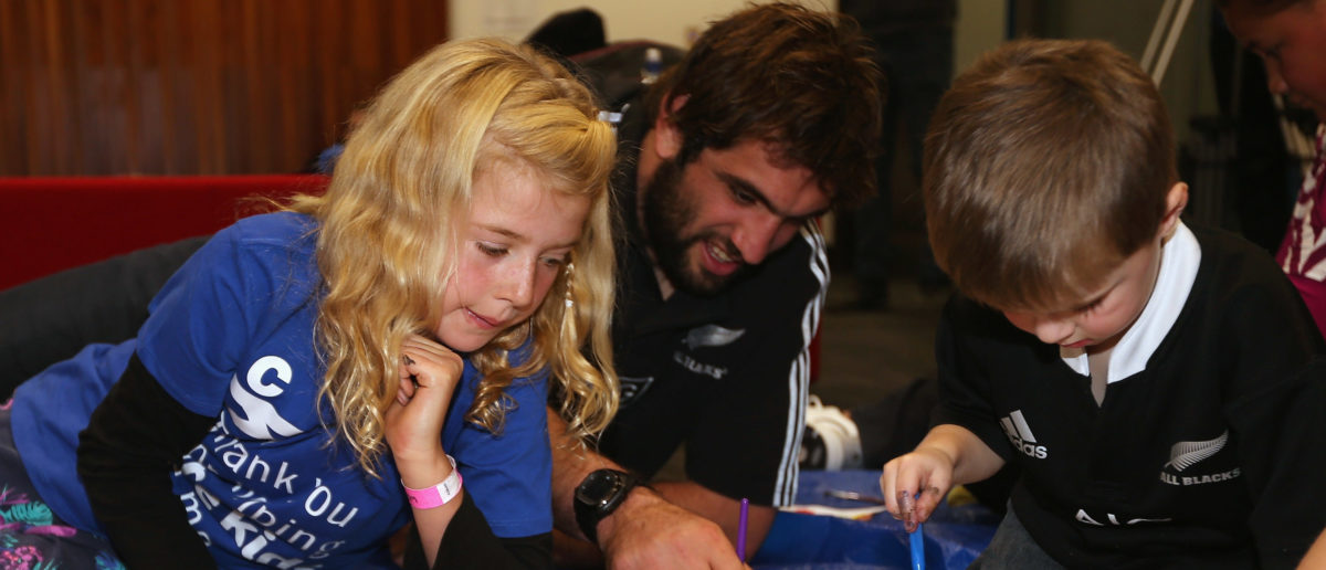 Alana Blow (L) who lives with ADHD and Marfan syndrome paints alongside All Black Sam Whitelock (R) during the New Zealand All Blacks 'Cure Kids' Appearance at Auckland University on June 2, 2014 in Auckland, New Zealand. Sandra Mu/Getty Images for Cure Kids