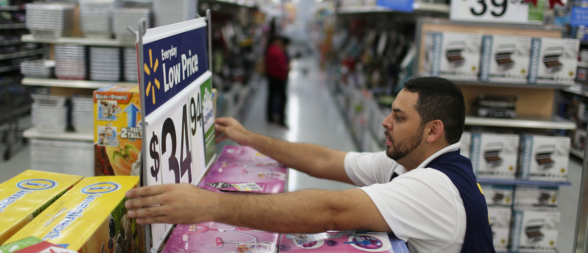 Jaime Vado fixes a display in the isle at a Walmart store as they prepare for Black Friday shoppers on November 24, 2015 in Miami, Florida. Black Friday, which is the day after Thanksgiving, is known as the first day of the Christmas shopping season and most retailers offer special deals on the day. Photo by Joe Raedle/Getty Images