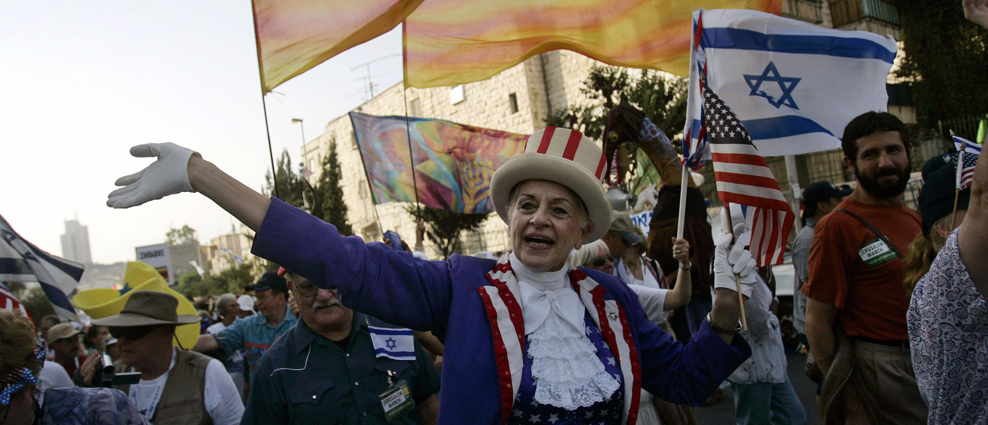 """A Christian Evangelical from the United States, dressed in an """"Uncle Sam"""" costume, waves to onlookers during a parade in celebration of the Jewish holiday of Sukkoth, in downtown Jerusalem 02 October 2007. Thousands of Christian Evangelical supporters of the Jewish state marched today during their annual parade marking the Jewish holiday of Sukkoth or the Feast of the Tabernacles. AFP PHOTO/DAVID FURST (Photo credit should read DAVID FURST/AFP/Getty Images)"""