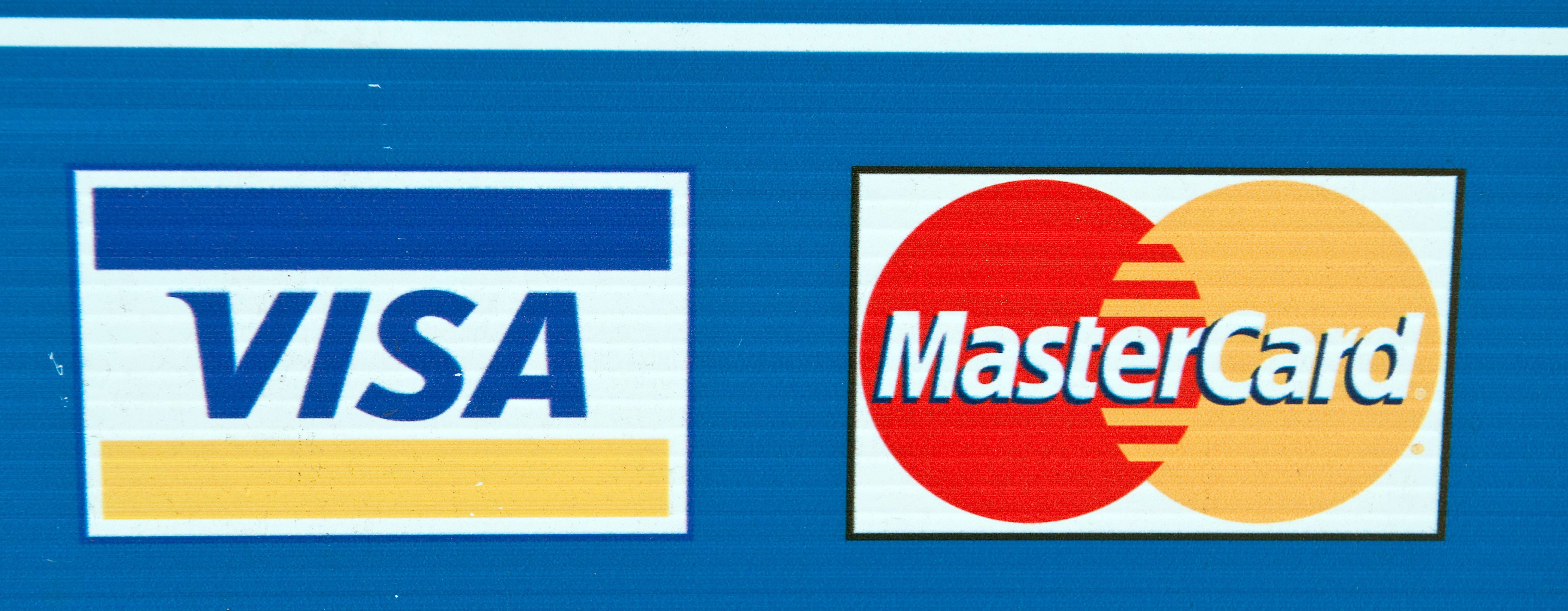 Visa and MasterCard credit card logos are seen on a sign in Washington on March 30, 2012. Credit card giants Visa and MasterCard were scrambling to thwart cyber crooks who looted a massive trove of precious account data, evidently from a payment processor in New York. Gartner analyst Avivah Litan said that industry sources revealed that numbers from more than 10 million credit card accounts were stolen in the breach, with the entry point being a New York City taxi and parking garage company. AFP PHOTO/Nicholas KAMM / AFP PHOTO / NICHOLAS KAMM (Photo credit should read NICHOLAS KAMM/AFP/Getty Images)