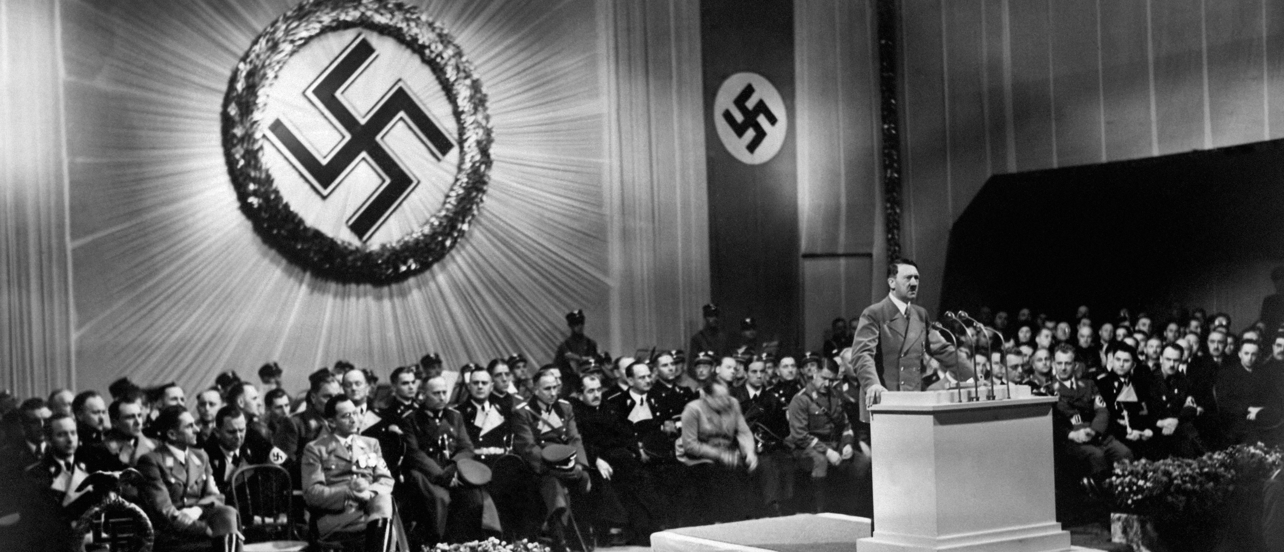 A picture dated 1939 shows German nazi Chancellor and dictator Adolf Hitler giving a speech during a meeting with nazi high rank officials seated under a large swastika. AFP PHOTO / FRANCE PRESSE VOIR (Photo credit should read -/AFP/Getty Images)