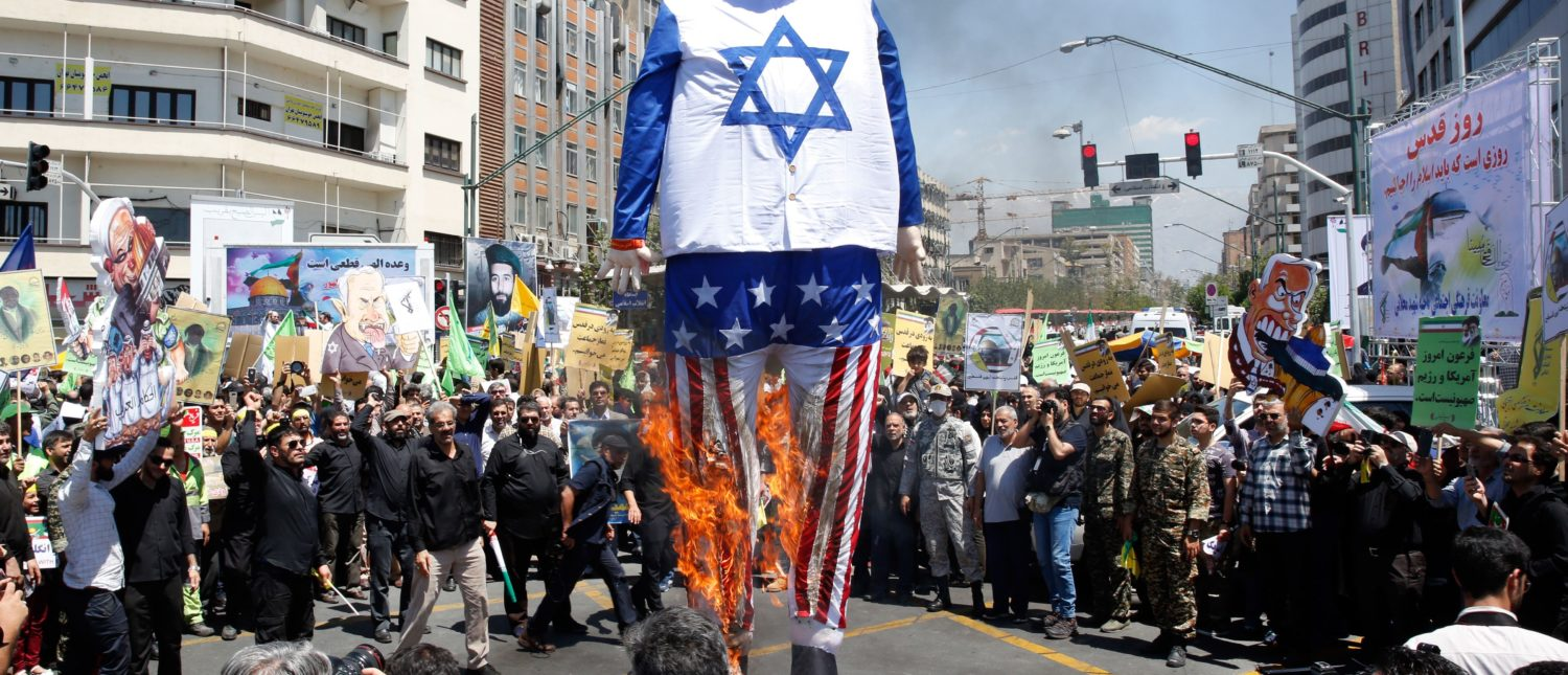 """Iranian protesters burn an effigy of US President Donald Trump dressed in an Israeli flag during a rally to mark """"Qods day"""" (the day of Jerusalem), an annual day of demonstrations against Israel first initiated in 1979 to fall on the last Friday of the holy month of Ramadan, in Tehran on June 8, 2018. (Photo by STR/AFP/Getty Images)"""