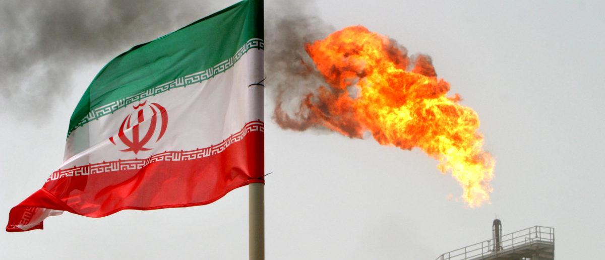 A gas flare on an oil production platform in the Soroush oilfields is seen alongside an Iranian flag in Iran, July 25, 2005. REUTERS/Raheb Homavandi/File Photo