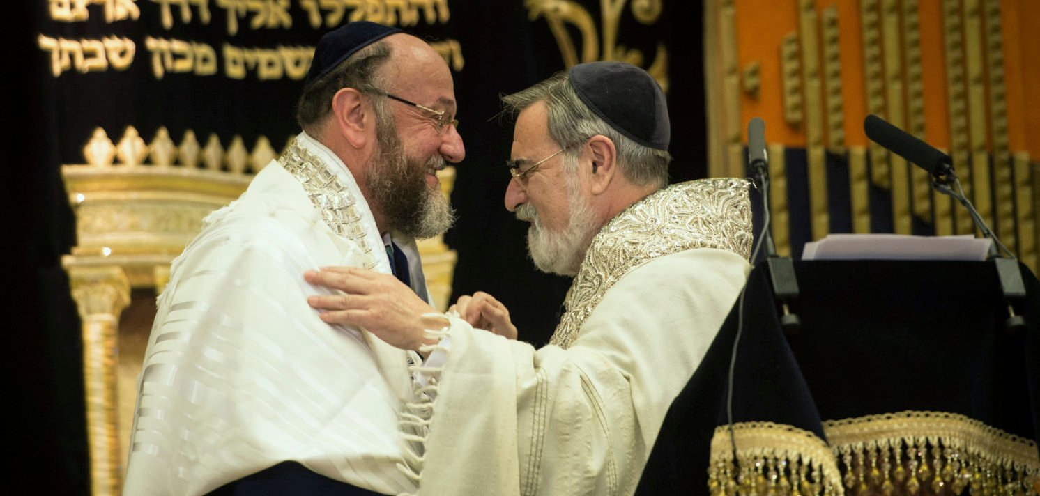 Former chief rabbi, Jonathan Sacks (R), congratulates the new chief rabbi, Ephraim Mirvis, during a ceremony at St John's Wood Synagogue in London September 1, 2013. Britain's new chief rabbi, Mirvis, was sworn in on Sunday, vowing to remain traditional by barring women rabbis and same-sex marriage and facing a struggle to unite the nation's polarised Jewish community. REUTERS/Stefan Rousseau/pool