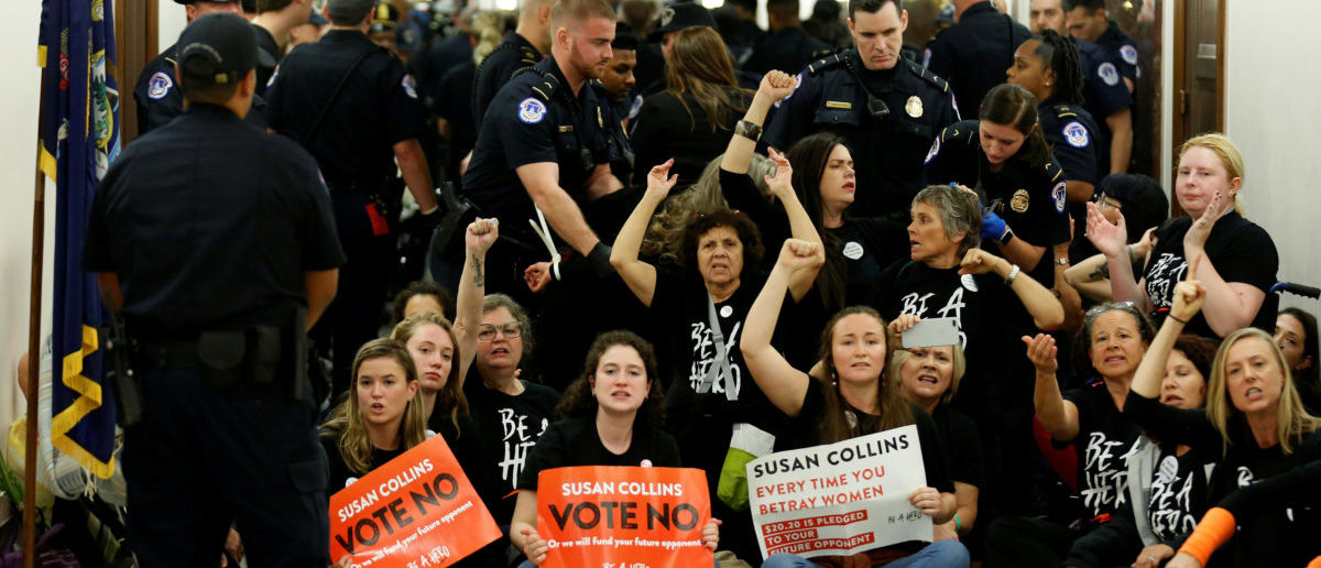 Demonstrators chant before being arrested as they protest against U.S. Supreme Court nominee Brett Kavanaugh in front of the office of Senator Susan Collins (R-ME) on Capitol Hill in Washington, U.S., September 24, 2018. REUTERS/Joshua Roberts
