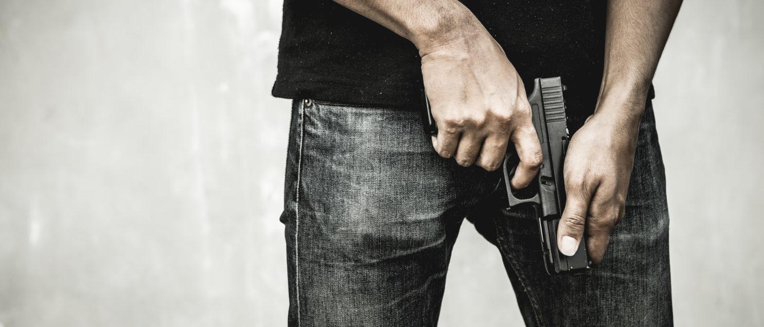 Man holding a gun (Shutterstock/BR Photo Addicted)