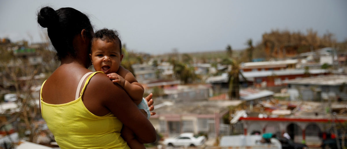 Ysamar Figueroa carrying her son Saniel, looks at the damage in the neighbourhood after the area was hit by Hurricane Maria, in Canovanas, Puerto Rico September 26, 2017. REUTERS/Carlos Garcia Rawlins/File Photo