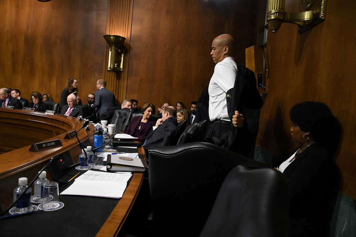 Sen. Cory Booker (D-NJ) takes off his jacket after the Democrats walked out in protest from the Senate Judiciary Committee meeting to vote on the nomination of Brett M. Kavanaugh to be an associate justice of the Supreme Court of the United States in Washington, September 28, 2018. REUTERS/Mary F. Calvert