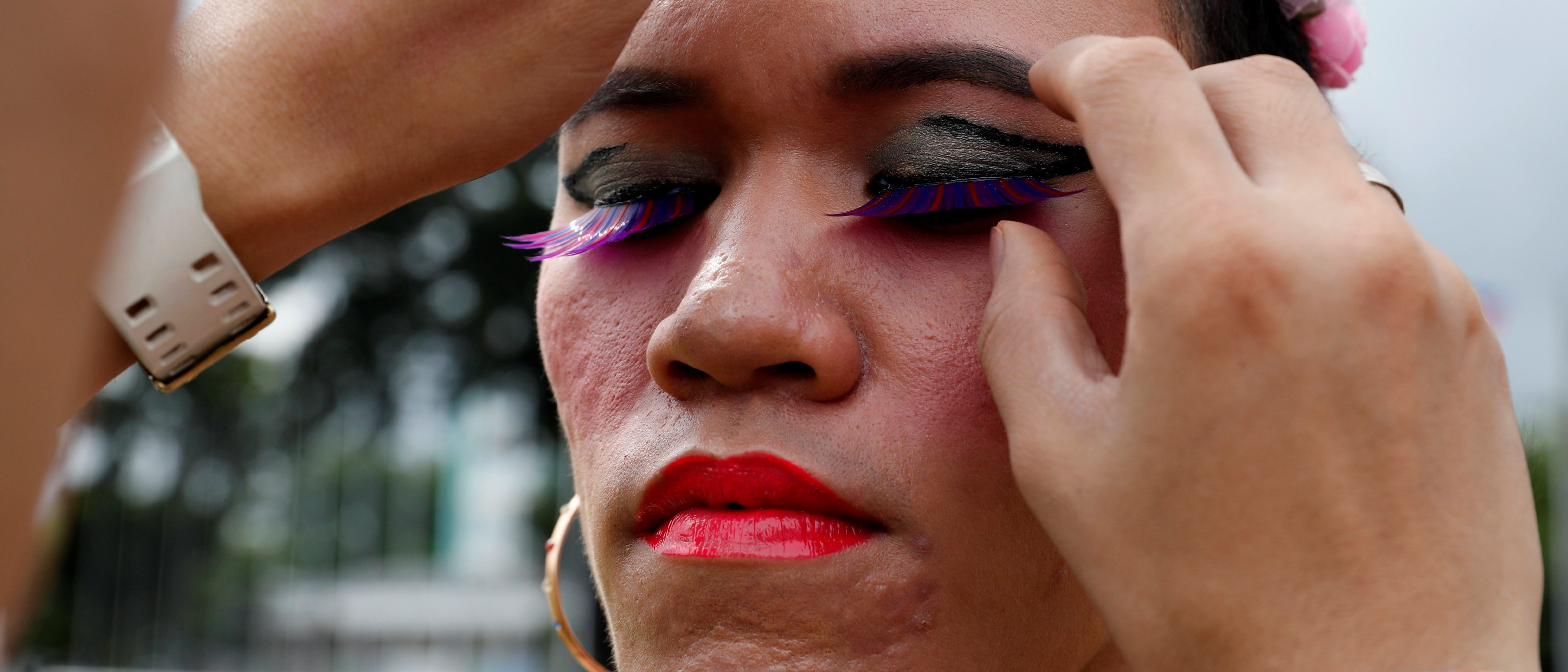 A colleague fixes an eyelashes of a transgender person before the start of a Gay Pride parade in Marikina, Metro Manila, in Philippines June 30, 2018. REUTERS/Erik De Castro - RC156DABFC40