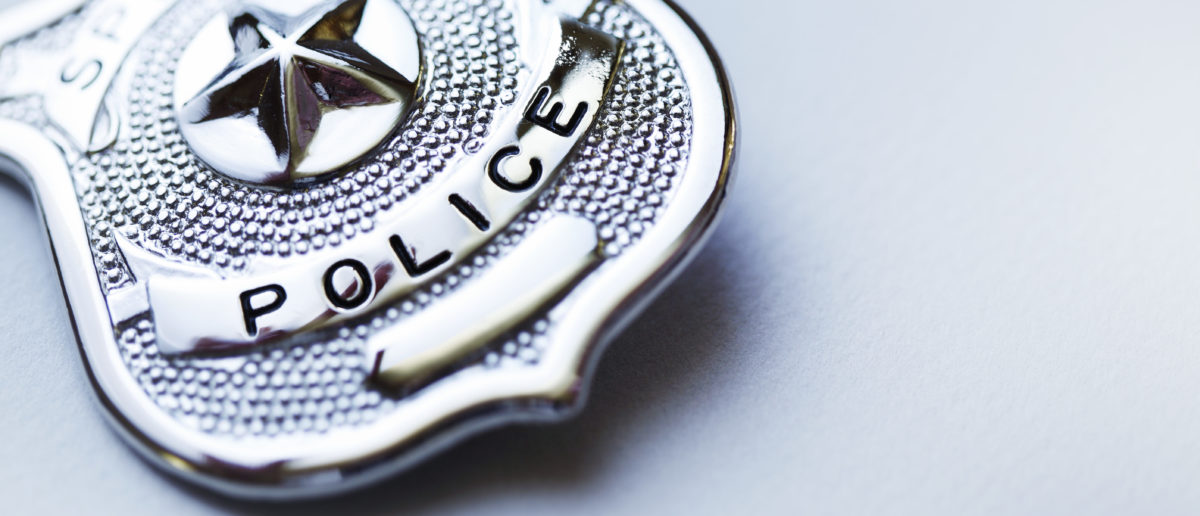 A police badge rests on a surface. Shutterstock image via user heliopix